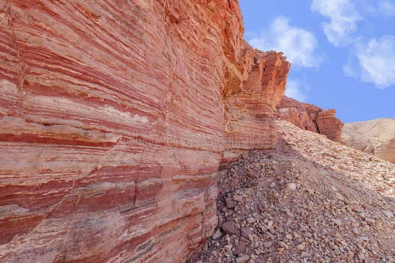Surface of a crumbling hill with multi-colored layers of rock. Red Canyon Israel stock photography