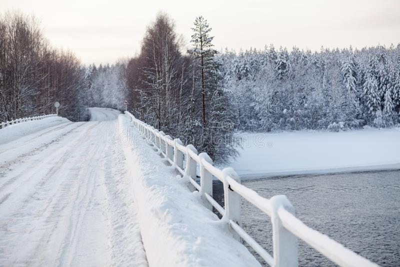 Surface de Milou de route de campagne vide sur le pont à travers une rivière, saison d'hiver photos stock