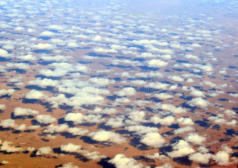 The surface of the earth and clouds from above. stock photo