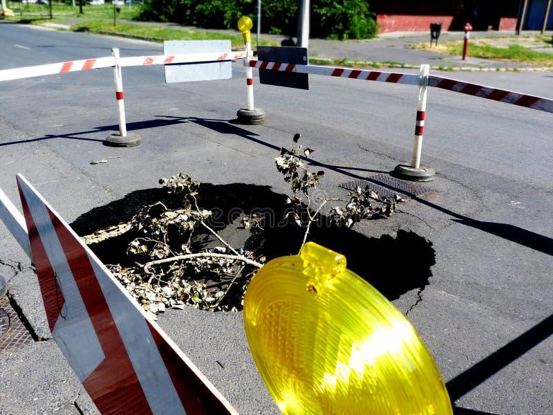 Surface effondrée de route goudronnée avec le grand cratère ci-dessous entouré par la barrière en bois rayée photos libres de droits