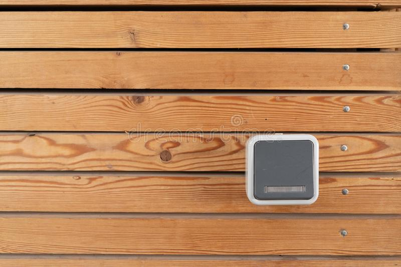 Surface of a freshly painted planking of a facade of horizontal wooden slats in the color mahogany and one 220 volt sockets. Wooden structure royalty free stock image