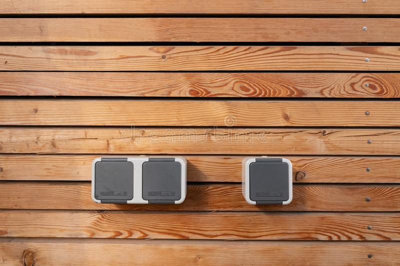 Surface of a freshly painted planking of a facade of wooden slats in the color mahogany and three 220 volt sockets. Wooden structure royalty free stock photography