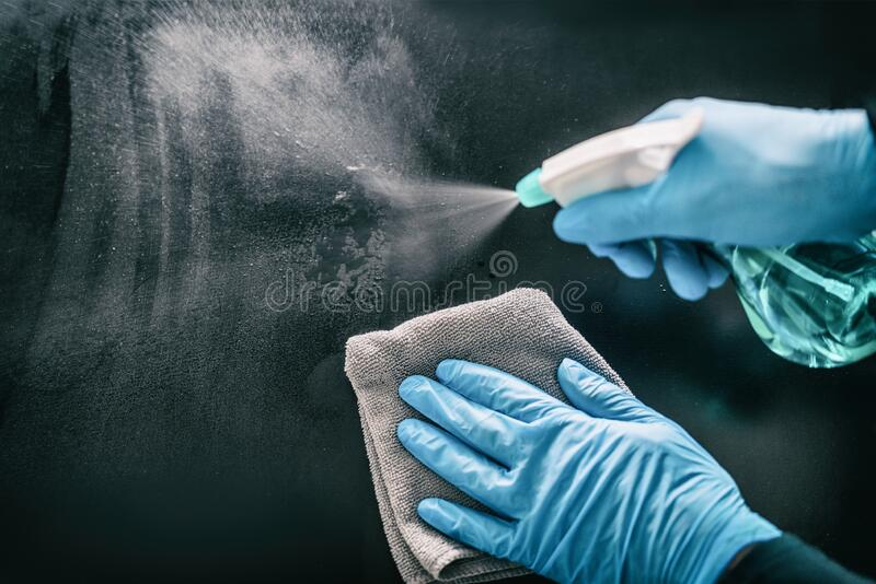 Surface home cleaning spraying antibacterial sanitizing spray bottle disinfecting against COVID-19 spreading wearing. Medical blue gloves. Sanitize surfaces royalty free stock photo