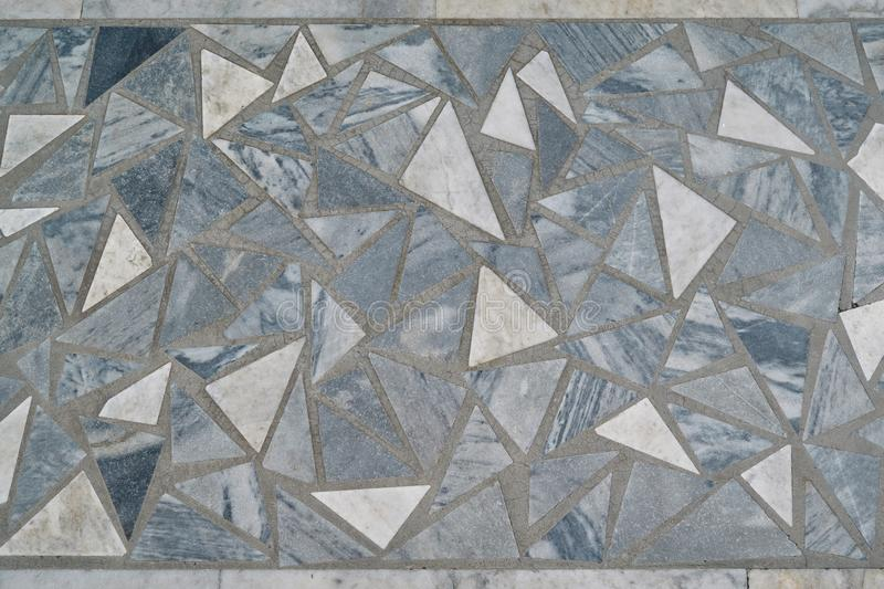The surface is laid with a mosaic of triangular tiles of various sizes stock image