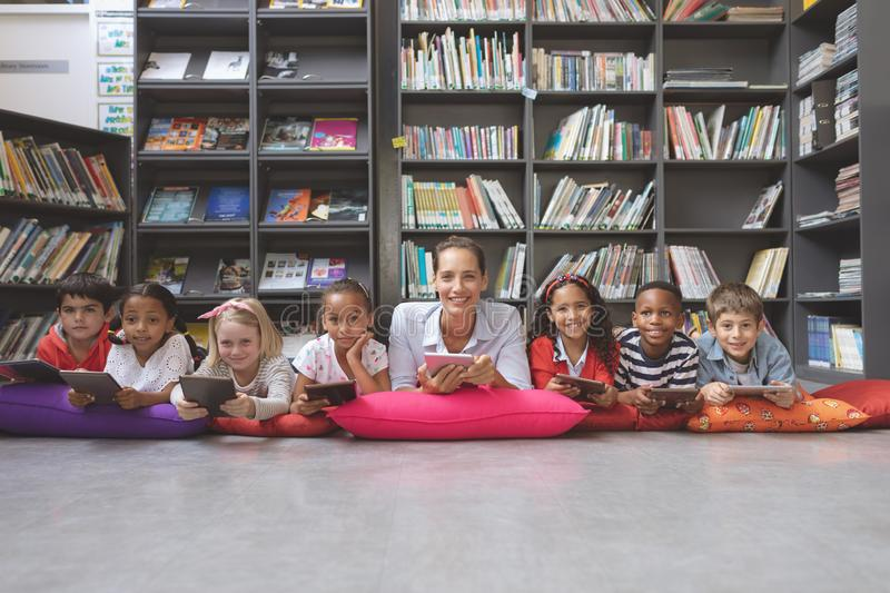 Happy schoolteacher lying with his school kids in a library stock photo