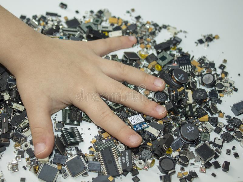 SMT components and a child hand over them. Surface mount components in bulk and a child`s hand over them royalty free stock images