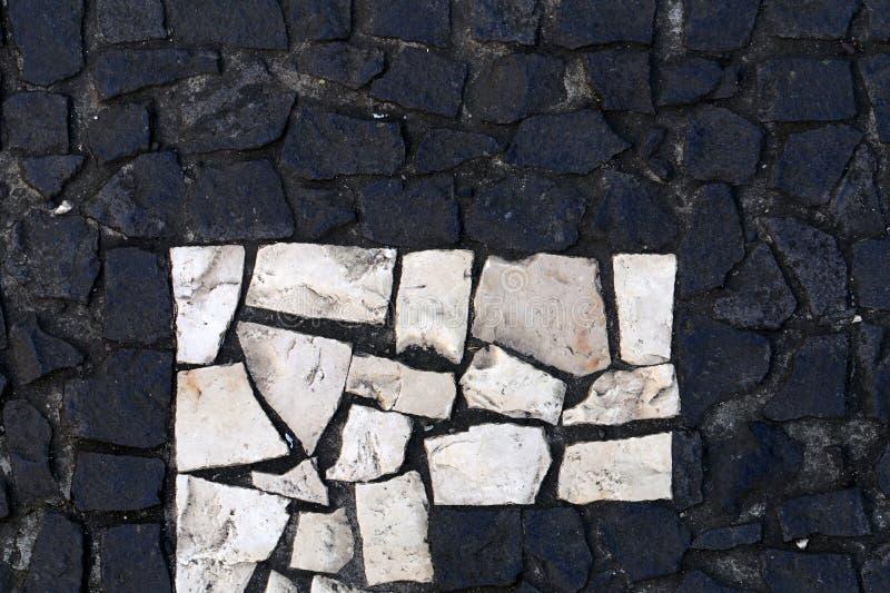 Surface noire et blanche d'un plancher extérieur fait de petits morceaux de tuile image stock
