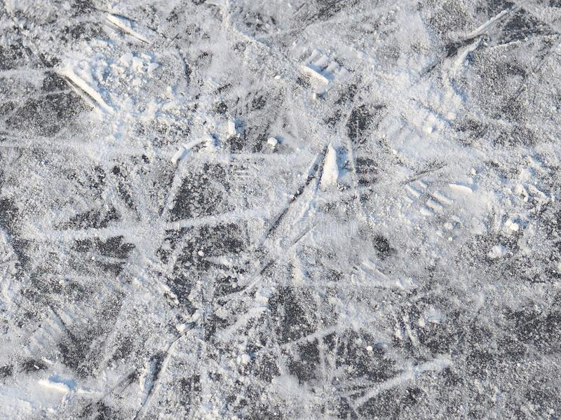 Surface of the outdoor skating rink. Marked with traces of skates and replete snow stock photography