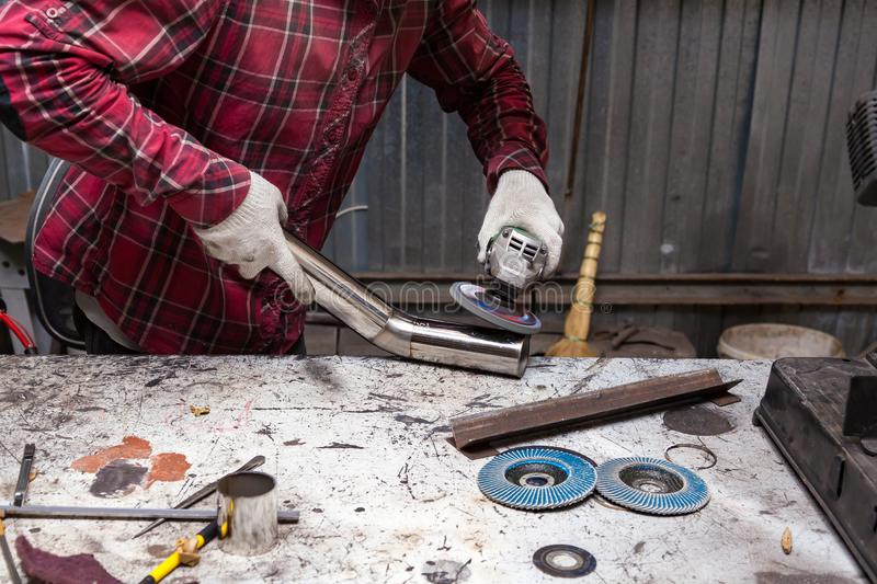 Surface preparation of stainless steel pipes using an angle grinder for further welding in an iron workshop. Industry and royalty free stock photos