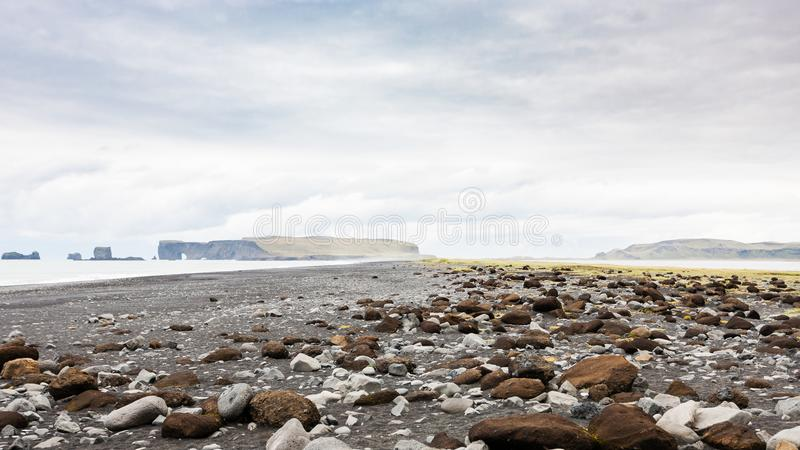 Surface of Reynisfjara Beach and Dyrholaey cape. Travel to Iceland - surface of Reynisfjara Beach and view of Dyrholaey cape in Iceland, near Vik I Myrdal royalty free stock images