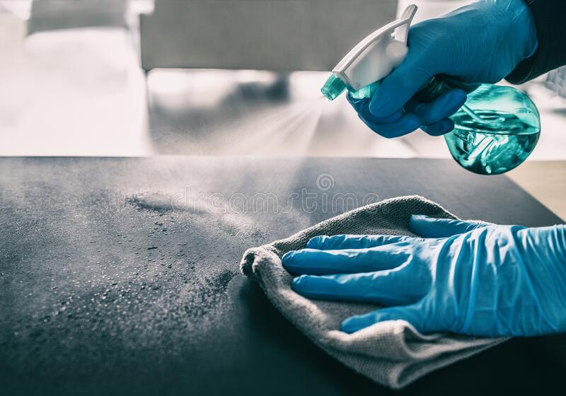 Surface sanitizing against COVID-19 outbreak. Home cleaning spraying antibacterial spray bottle disinfecting against. Coronavirus wearing nitrile gloves stock photos