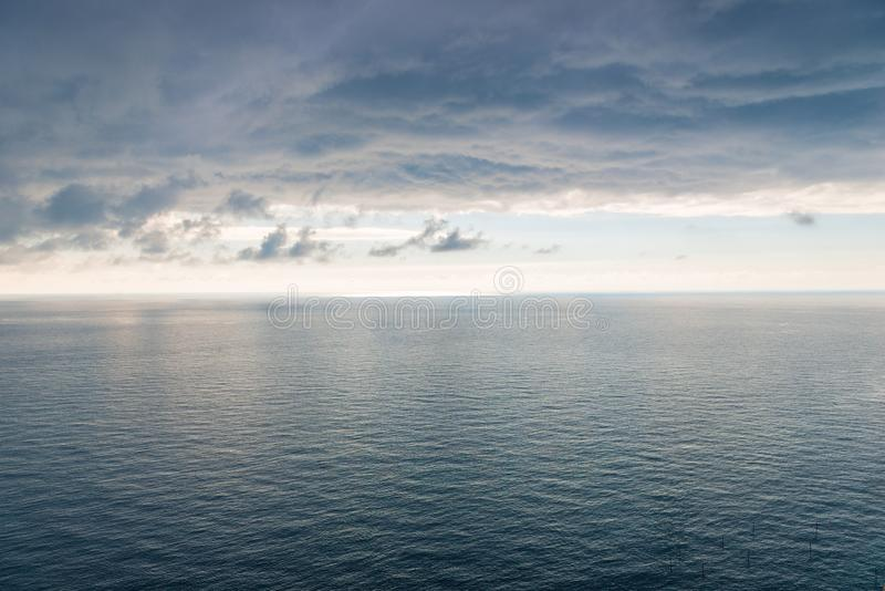 The surface of the sea with a slight ripple, a view of the horizon and heavy black rain clouds a beautiful landscape royalty free stock images