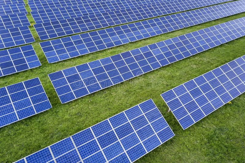 Surface of solar photo voltaic panels system producing renewable clean energy on green grass background.  stock photos