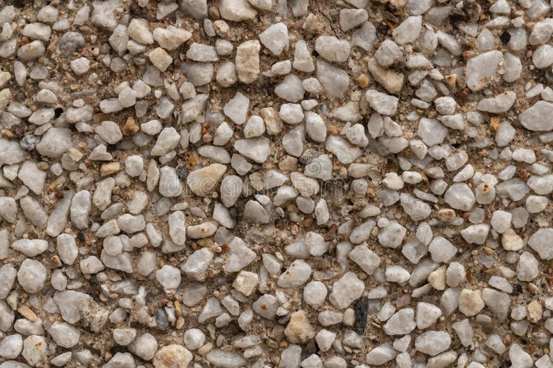 surface structure created by spraying, sand sifted painted crimson and cream small stones, gravel walls, building facades, the stock photo