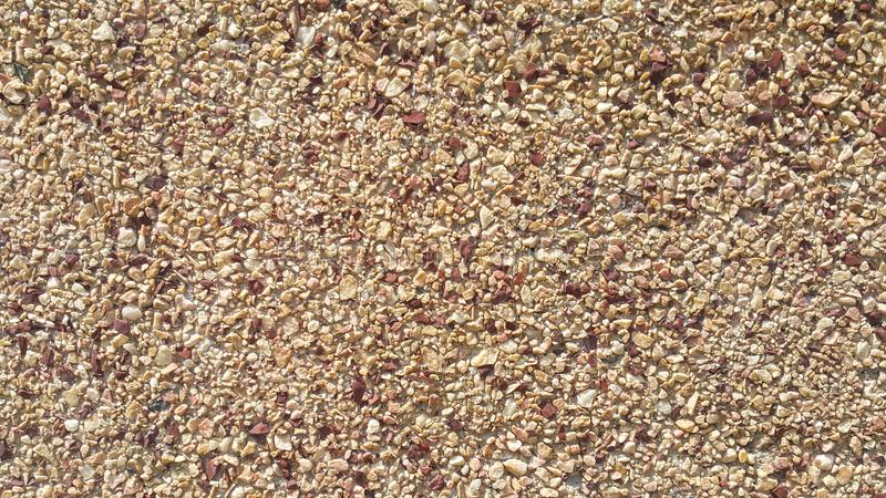 Surface structure created by spraying, sifted sand painted crimson and cream small stones royalty free stock images