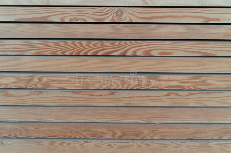 Surface of a transparent painted planking of a facade of horizontal wooden slats. Wooden structure royalty free stock image