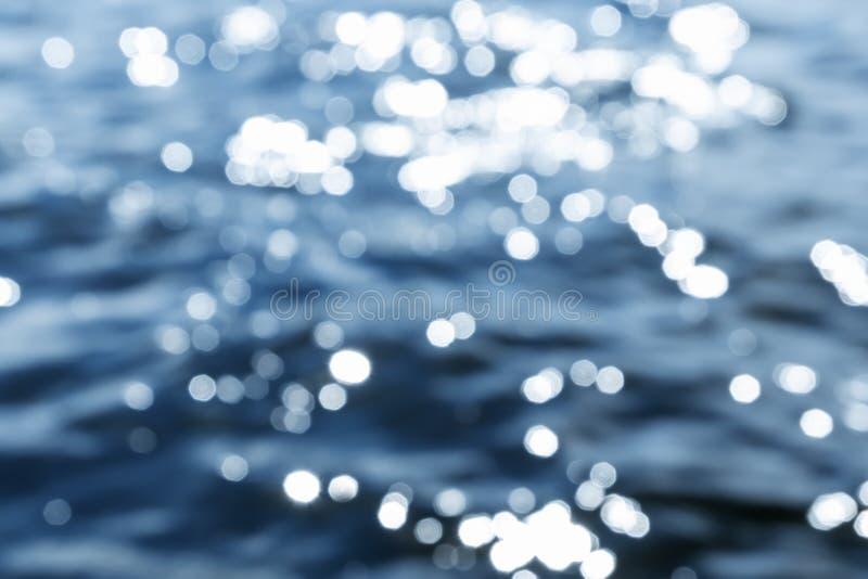 surface vatten f?r guld- krusningar bakgrundsblurblomma inom som looks s Blått hav med solilsken blick royaltyfri foto