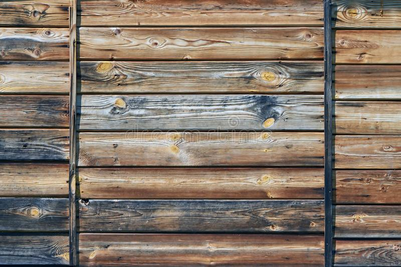 The surface of the wooden wall of the old house of several boards stock images