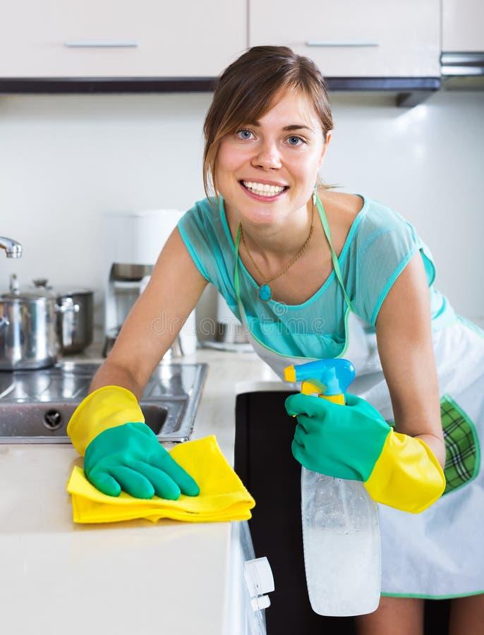 Surfaces adultes de saupoudrage de fille dans la cuisine photo stock