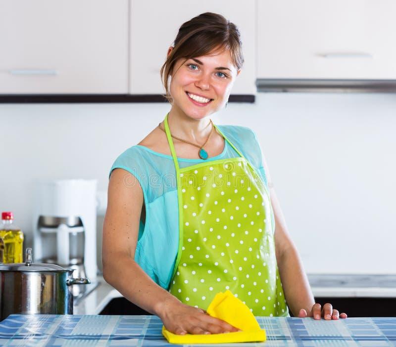Surfaces adultes de saupoudrage de fille dans la cuisine image libre de droits