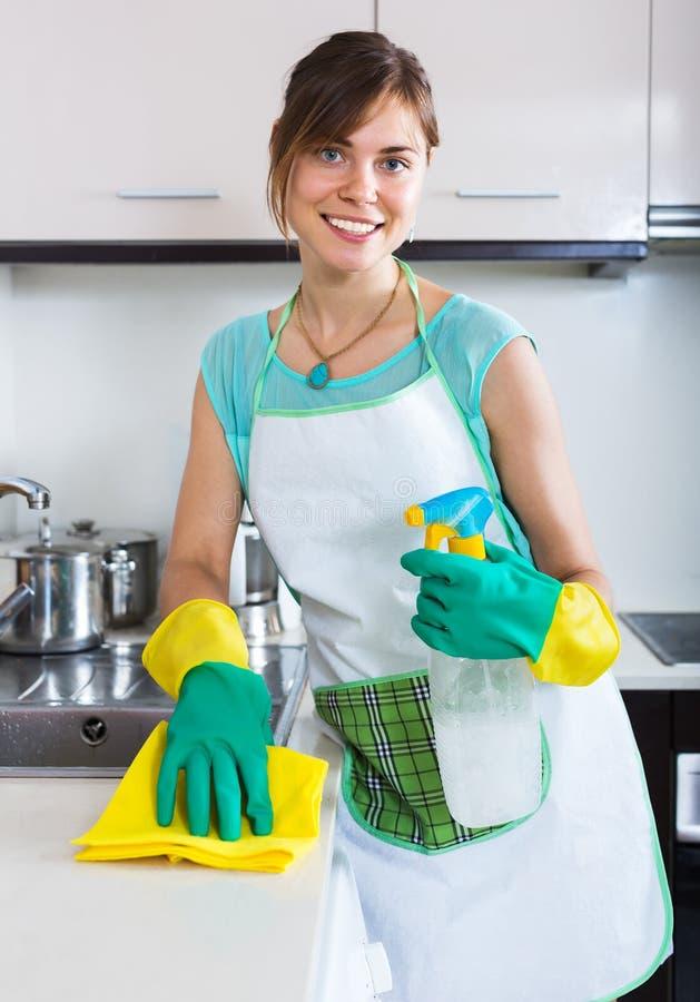 Surfaces adultes de saupoudrage de fille dans la cuisine photographie stock