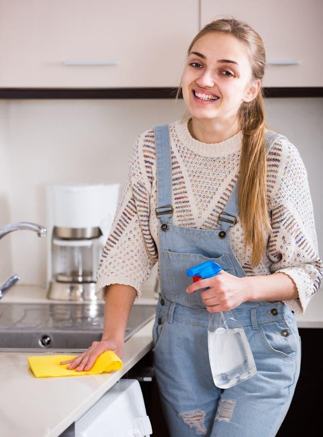 Surfaces adultes de saupoudrage de fille dans la cuisine résidentielle image libre de droits