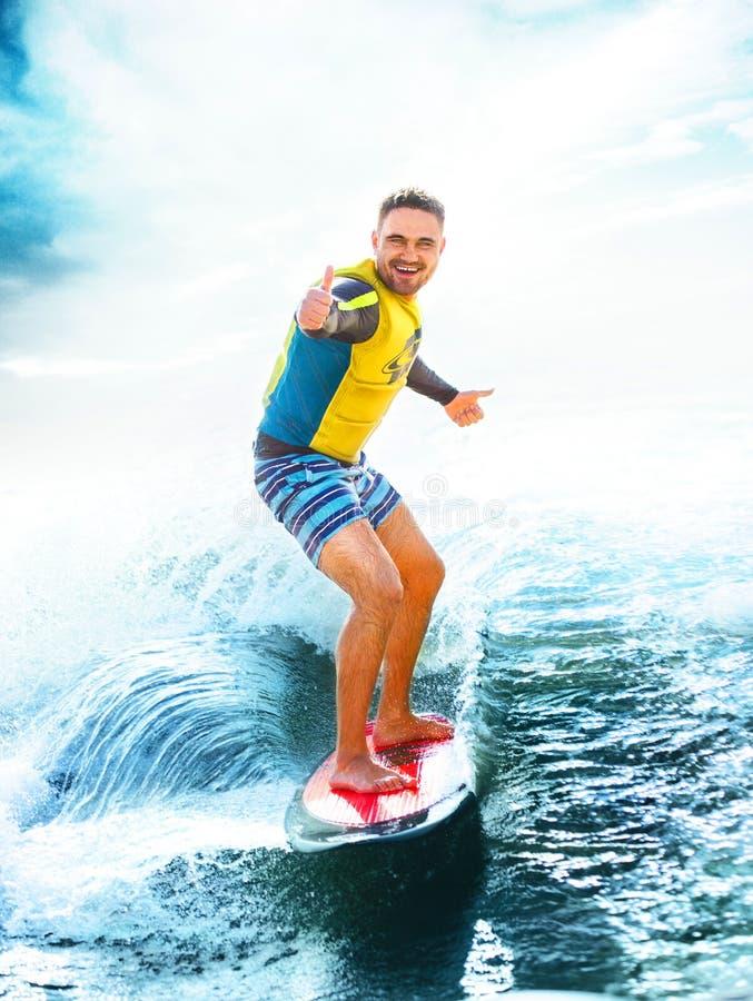 Surfando, oceano azul Polegares da mostra do homem novo acima no wakeboard imagens de stock royalty free