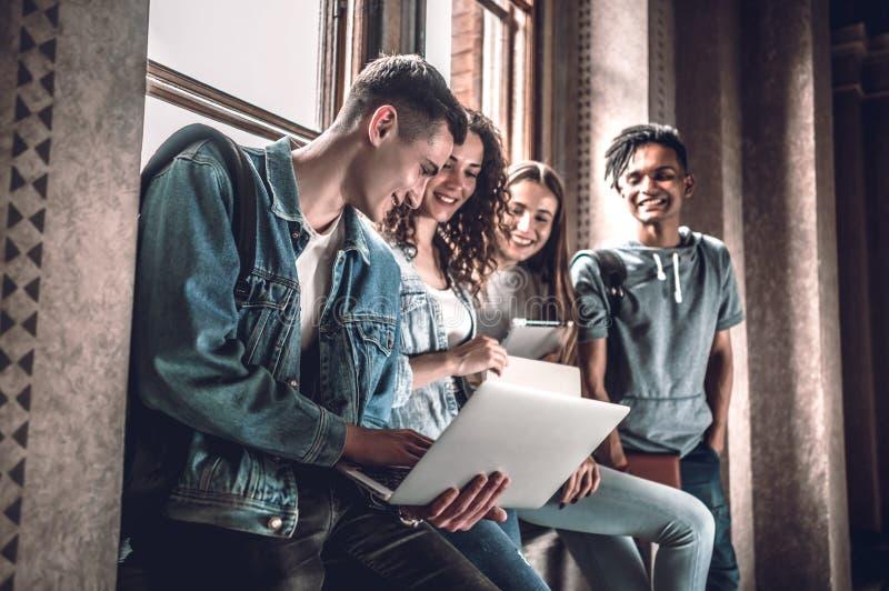 Surfando a rede junto Grupo de jovens felizes que trabalham junto e que olham o portátil ao sentar-se no peitoril da janela imagem de stock royalty free