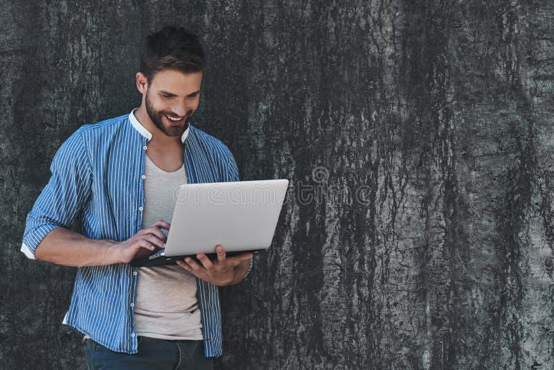 Surfant le filet dehors Jeune homme beau dans la tenue de détente futée travaillant sur l'ordinateur portable tout en se reposant images stock