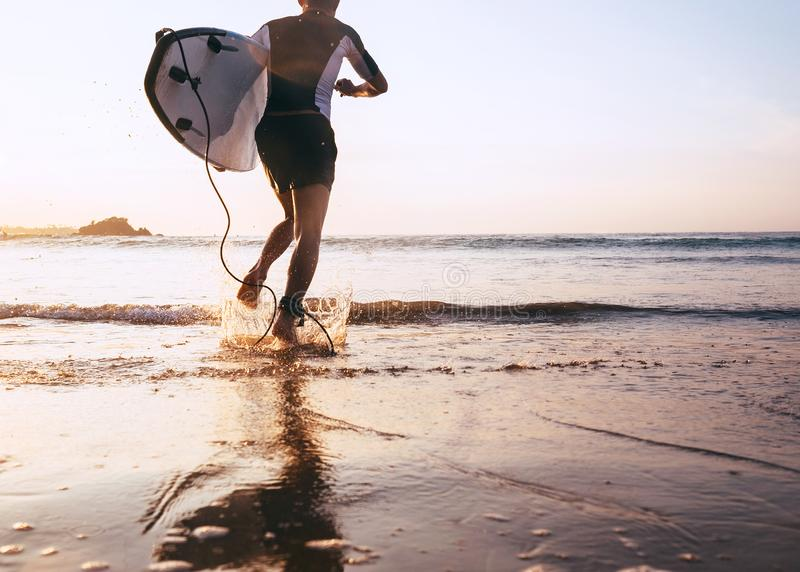 Surfare för ung man som tar surfingbrädan och spring med det långa bränningbrädet till vågor på bakgrunden för aftonsolnedgånghim royaltyfri fotografi