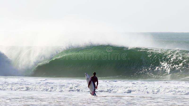 Surfare framme av en stor våg arkivbild