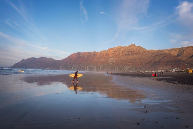 Surfare i den Famara stranden i Lanzarote, kanariefågelöar, Spanien royaltyfri fotografi