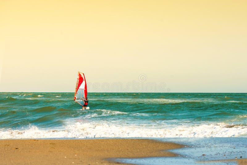 Surfare i havet på Kreta på solnedgång Vindsurfa i Heraklion Grekland royaltyfri bild
