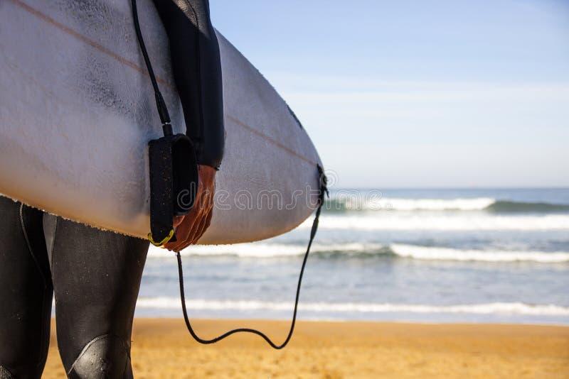 Surfare med hans bräde på stranden royaltyfri bild