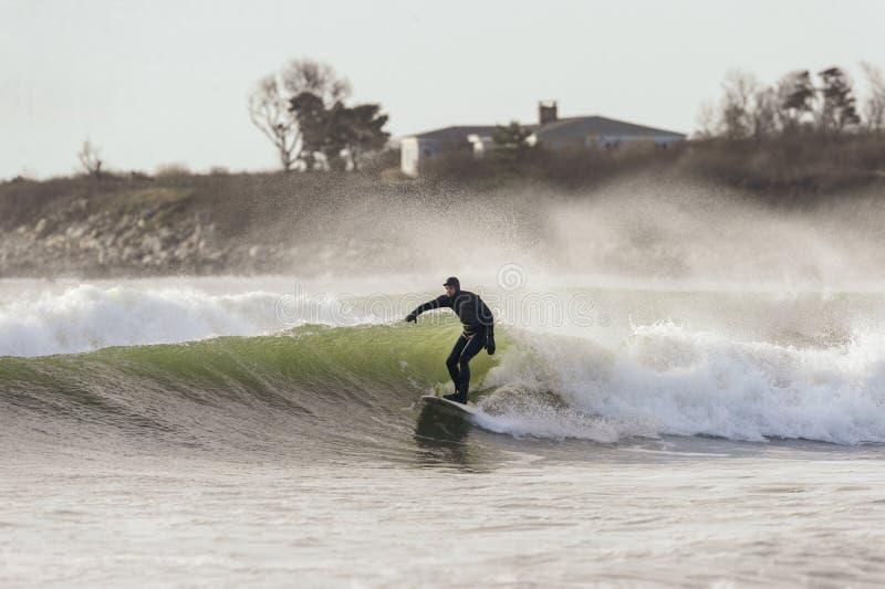 Surfare och sprej på blåsig dag arkivbild