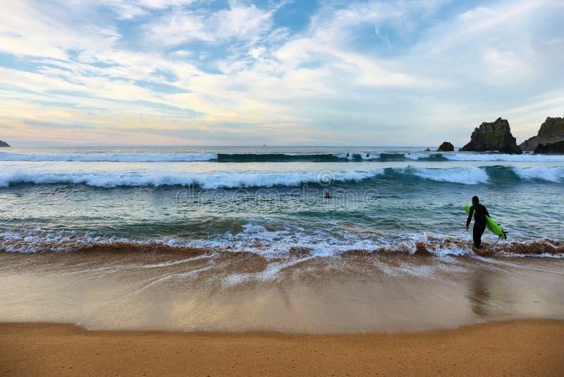 Surfare på solnedgången i den Laga stranden, baskiskt land, Spanien arkivbild