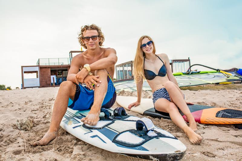 Surfare på stranden som ler par av surfare som går på stranden och har gyckel i sommar Extrem sport och arkivbild