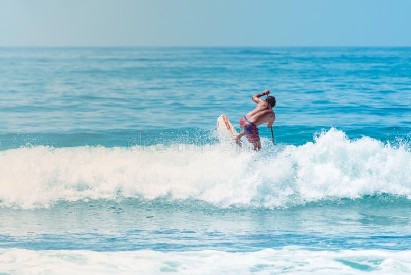 Surfare som hoppar en våg på den Sayulita Nayarit stranden royaltyfri foto