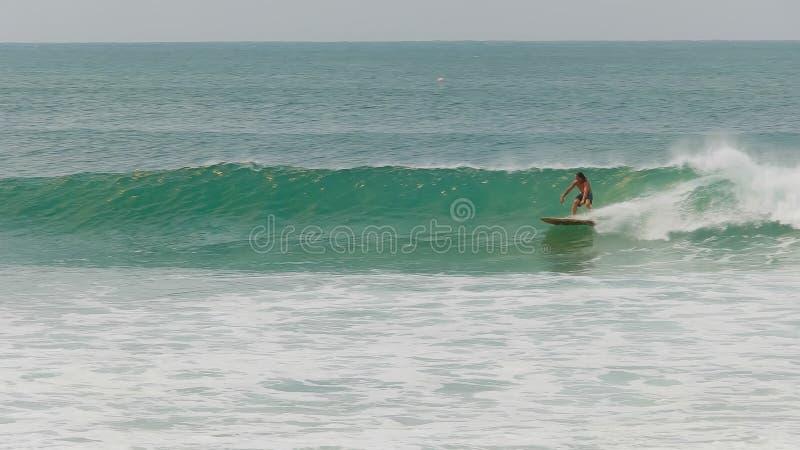Surfare som rider en våg på deras backhand- på greenmount, qld arkivbilder