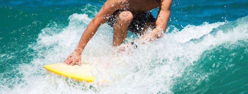 Surfare som sqauting låg ridning en våg royaltyfri foto