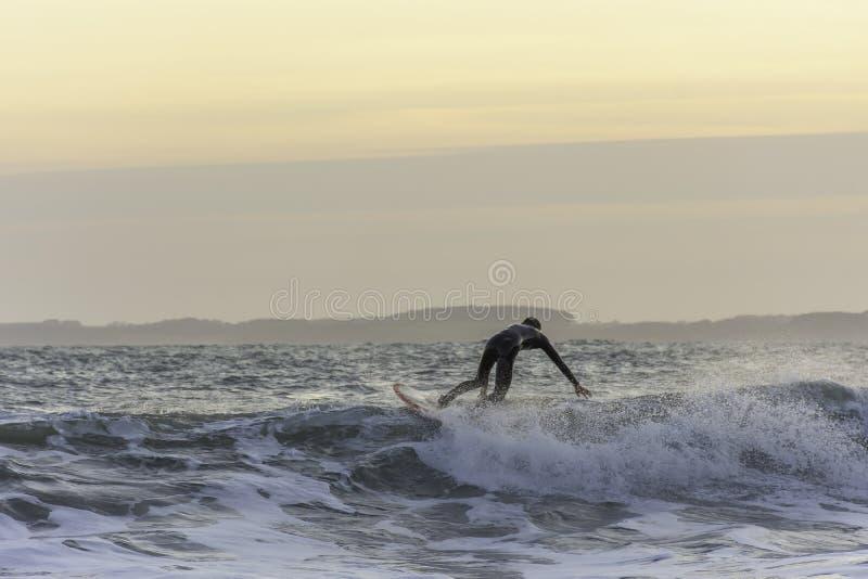 Surfare som trycker på vågen, medan fånga jämvikt under aftonbränning i det grova havet royaltyfria bilder