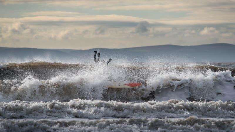 Surfare under en wipeout arkivbild
