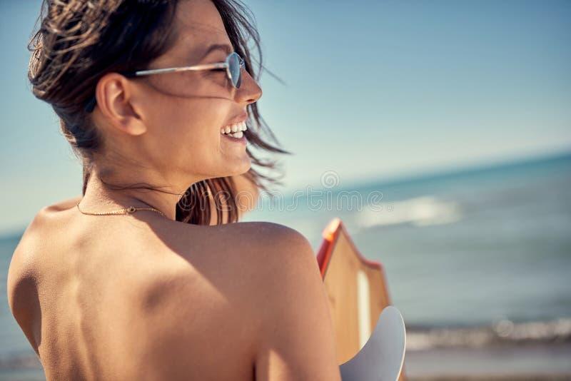 Surfareflicka Den sexiga kvinnan på stranden tillbaka beskådar konkurrensar som dyker pölsportar som simmar vatten arkivfoton