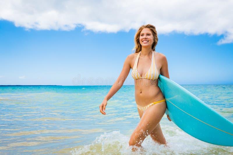 Surfareflicka i bikini med surfingbrädan royaltyfria foton