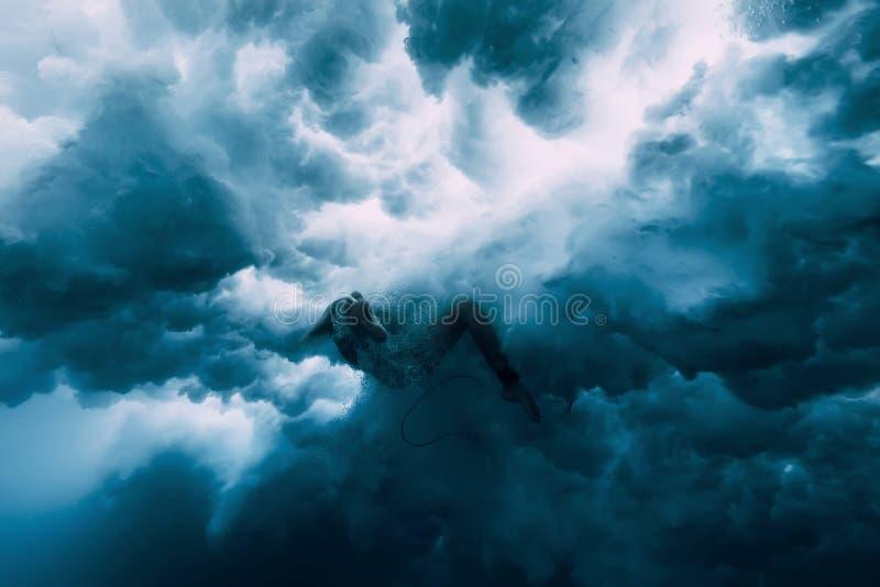 Surfareflicka med surfingbrädan under våg undervattens- wipeout royaltyfri bild