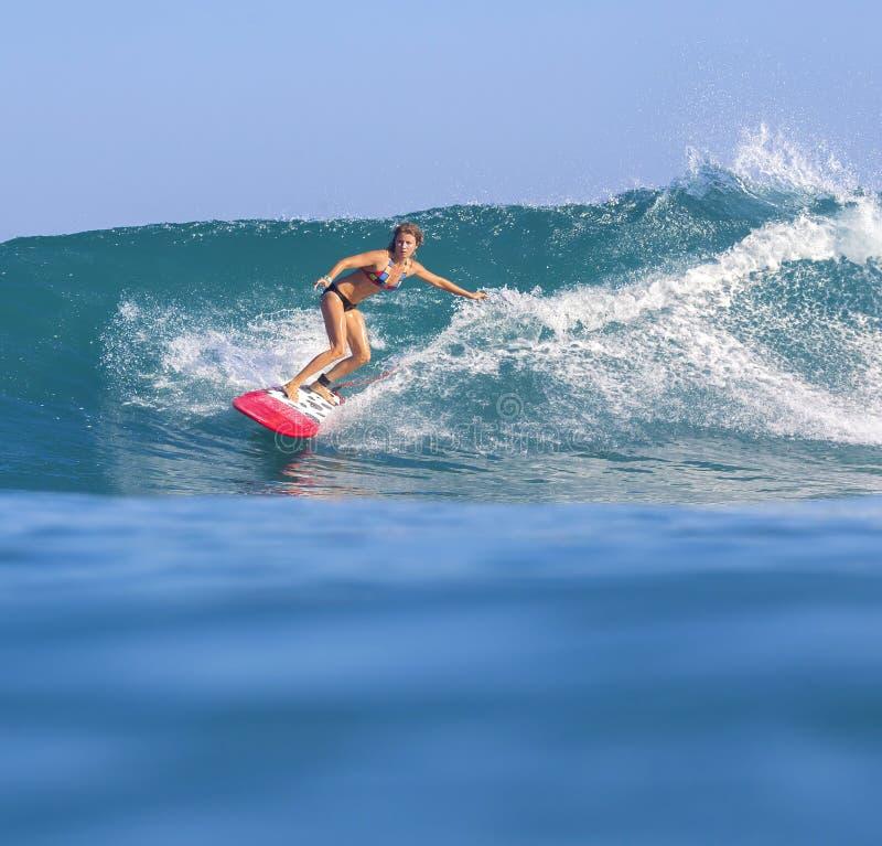 Surfareflicka på fantastisk blåttvåg fotografering för bildbyråer