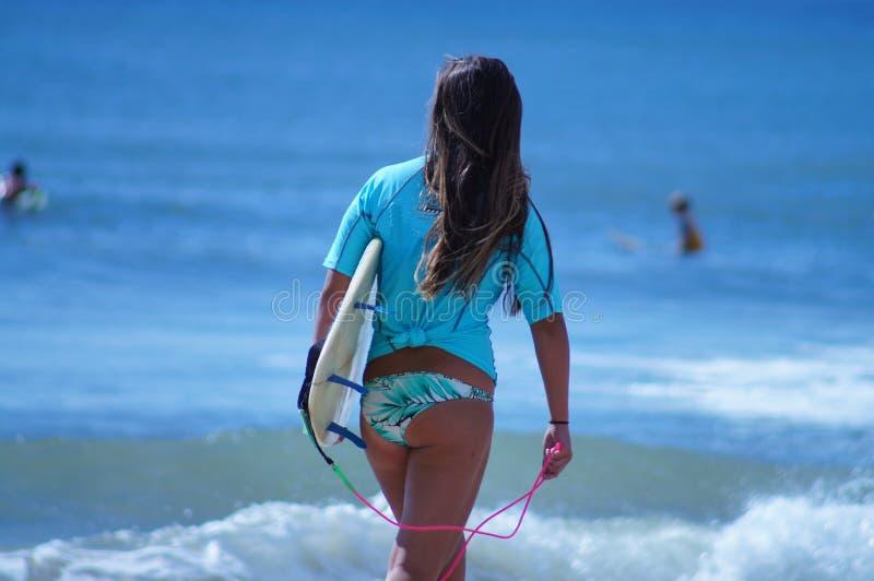 Surfareflicka som går med surfingbrädan på stranden i de yttre bankerna av NC royaltyfri foto