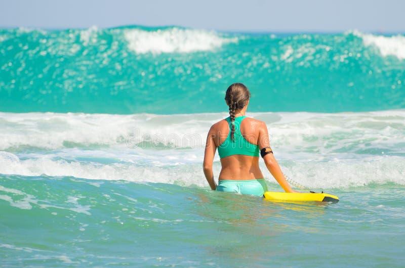 Surfareflickan - förkroppsliga surfa strandkvinnan som skrattar ha gyckel royaltyfri foto
