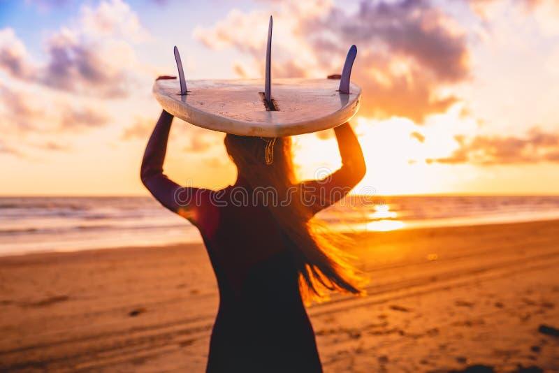 Surfareflickan med långt hår går till att surfa Kvinna med surfingbrädan på en strand på solnedgången eller soluppgång arkivbild