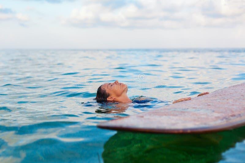 Surfareflickan på surfingbrädan har en gyckel, innan han surfar royaltyfri fotografi